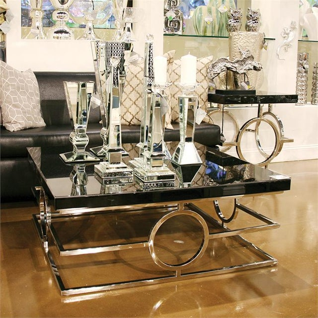 This Coffee Table features a stainless steel bar frame detailed with a circular design on each side. It is topped by a...