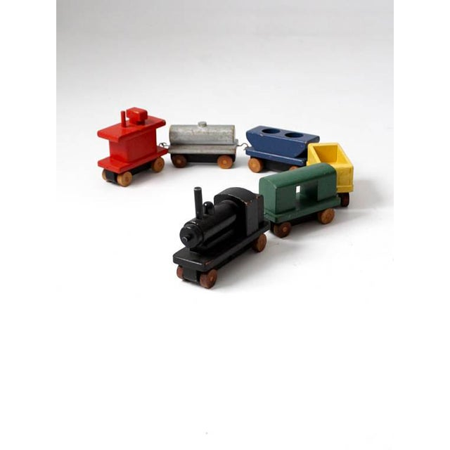 This is a vintage wooden toy train. It is a six piece pull set with an engine car and caboose. They have metal hooks and...