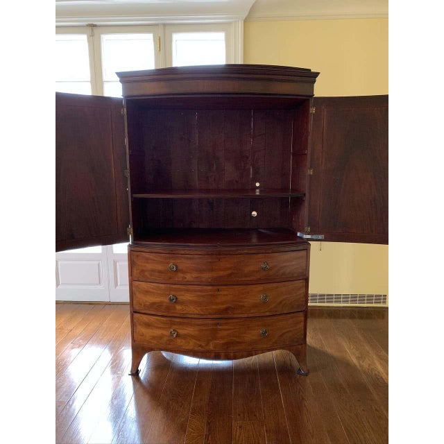 American linen press with bow front, chest on chest with three drawers above shelving. The piece has banded top veneer and...