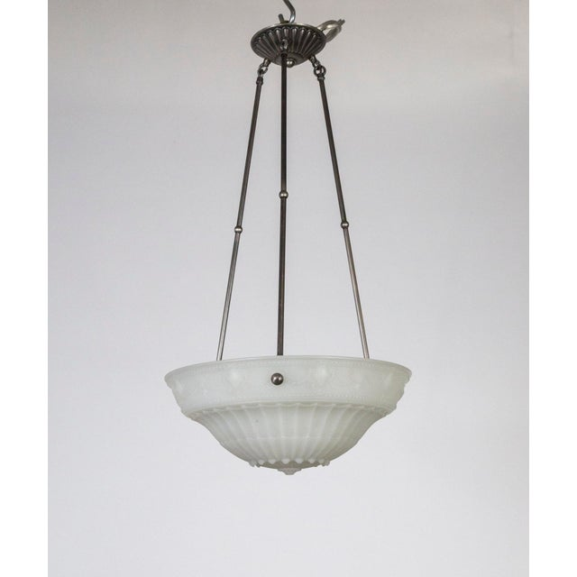 A heavy, milk glass bowl shade held with three, silver toned, brass stems. Matte glass molded with urn, garland, and...