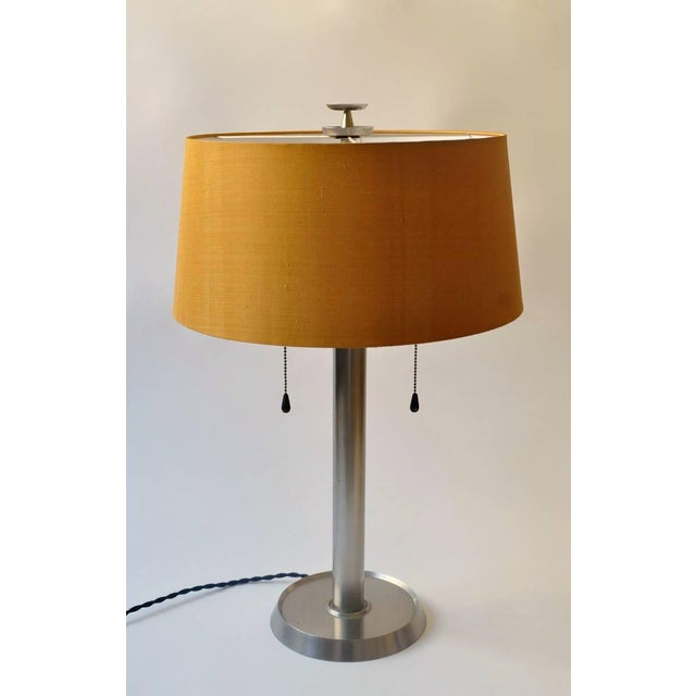 A fine Bronzewarenfabrik desk lamp, Zurich Switzerland. The warm hue of the refine silk shade balances the conservative...