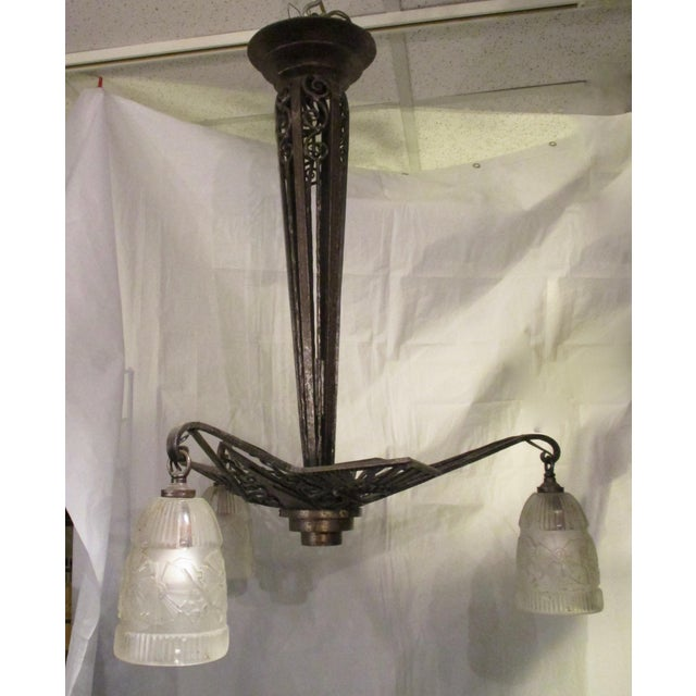 Art Modern French iron fixture . Three frosted glass shades over candelabra sockets. Very light and a elegant form.