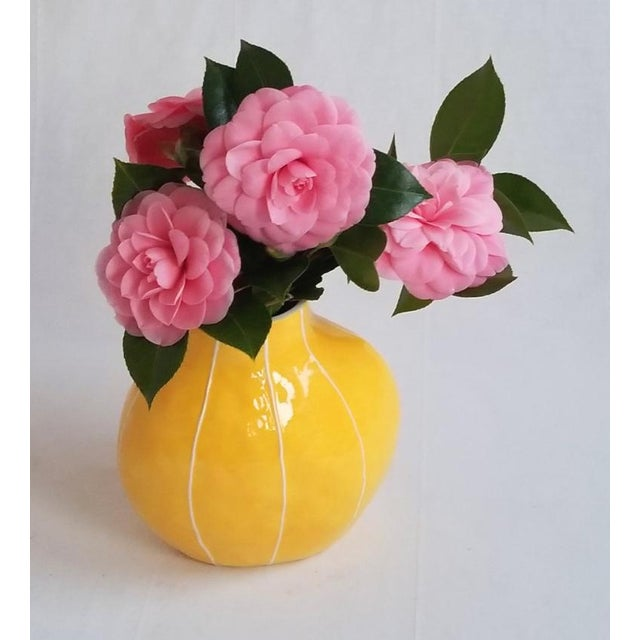 This bright, yellow vase has a modern, organic shape. It is handmade with a softly textured surface that catches and...
