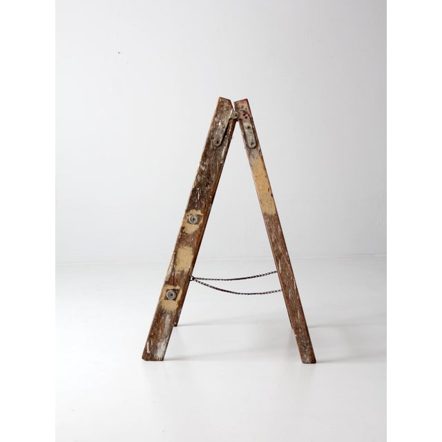 This is a vintage wooden folding ladder. Paint splatter and drips color the short wood ladder. It features a slender chain...
