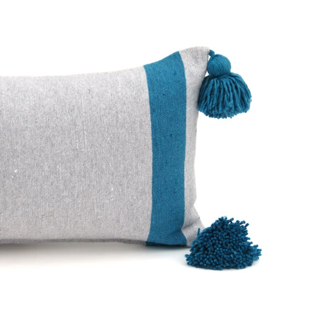 Handwoven Moroccan grey cotton pillow with turquoise pom poms. Custom down alternative insert and zipper closure. Matching...