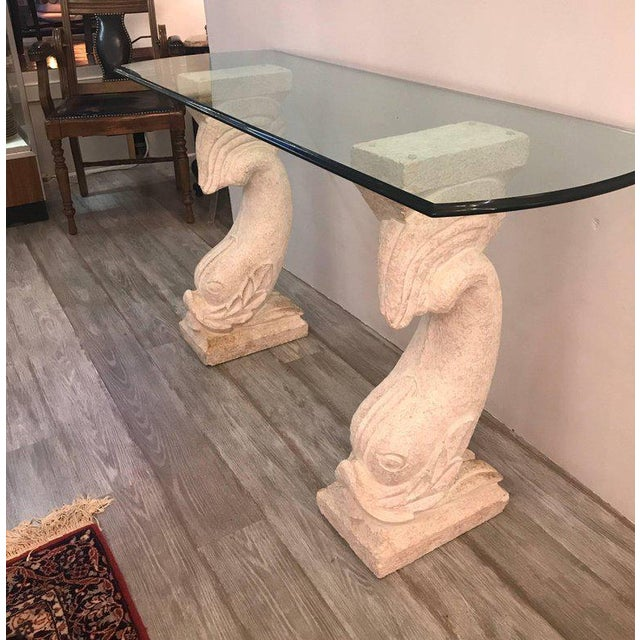 Whimsical dolphin motif console table. The two cultured stone bases with a stippled finish supporting a thick ogee edge...