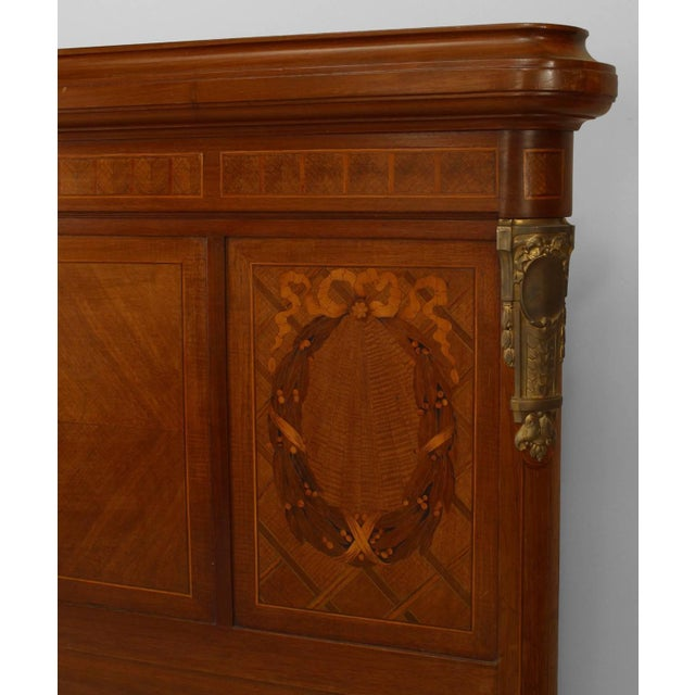French Louis XVI style queen size mahogany bed with extensive marquetry inlay with a ribbon pattern and bronze trim...