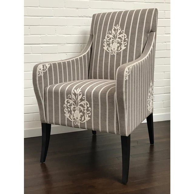 A heavy wool mélange yarn is embroidered as a large scale medallion across a natural striped background on this sleek...
