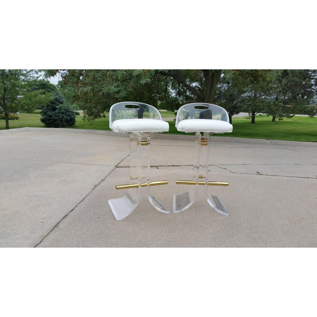 Absolutely dynamite pair of 1970's Charles Hollis Jones style lucite barstools with brass footrest and...