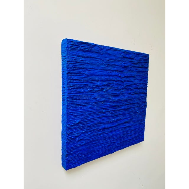 Ripples of waves, bold cobalt blue with hints of reflective colors under the waves. Signed and dated by artist.