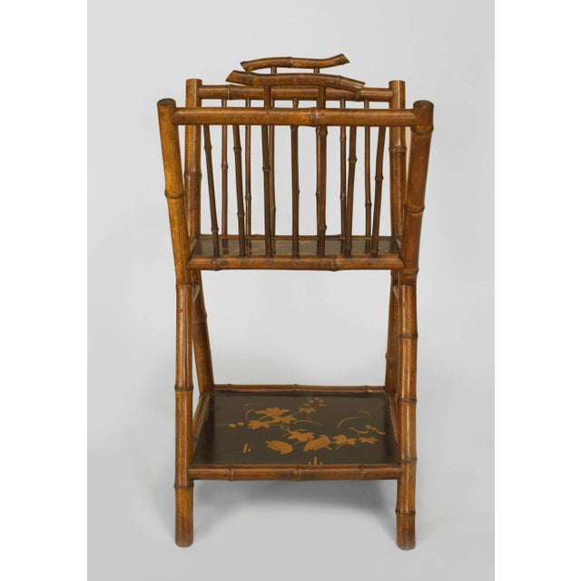 English Victorian bamboo magazine rack with black-lacquered and decorated shelf and spindle design sides.
