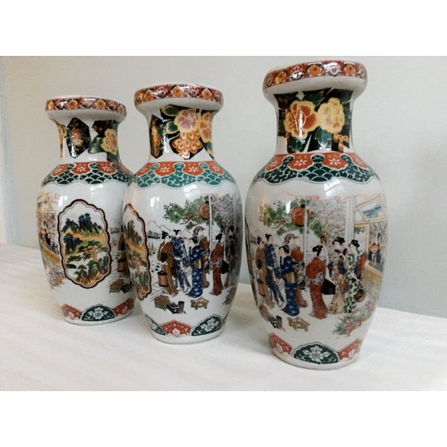 "Set of three ceramic glazed vases marked ""Gold Satsuma"", featuring a mosaic-like collage of various Asian figures and..."
