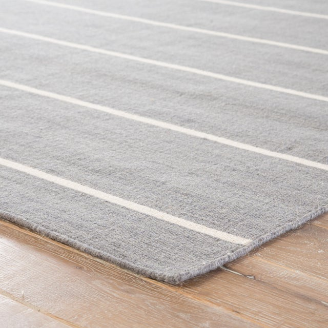 Classic with a bold stripe, this heathered gray and bright white flatweave area rug lends traditional charm to any space....