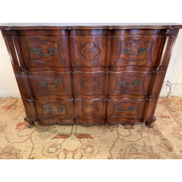 Handsome and solid mahogany dresser having serpentine front with conforming top and apron, resting on scroll feet. Its...