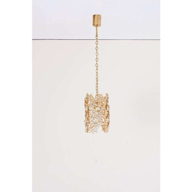 One of Three Palwa Gilded Brass and Crystal Glass Encrusted Pendant Lamps, Model S107. The lamps are handmade and in...