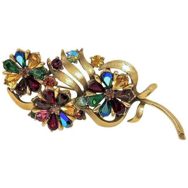 Circa 1960s Coro brooch in a floral and leaf motif done in a rich gold-tone brushed metal. It is set with faceted glass...