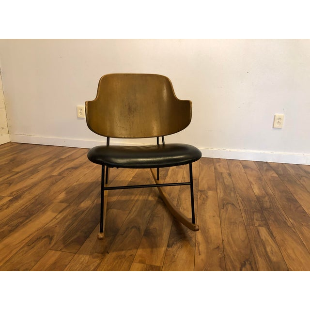 Mid century Ib Kofod Larsen penguin shell rocking chair with steel frame, leather wrapped seat and wood rocker glides....