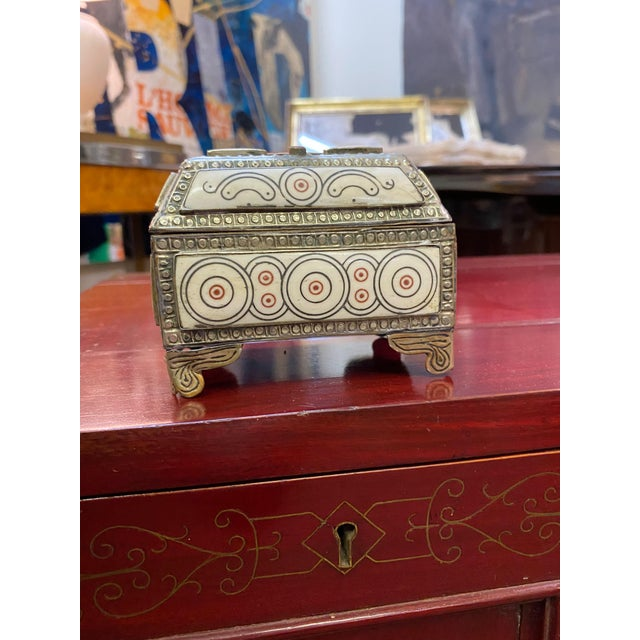 A decorative silver box with inlaid stones from Morocco.