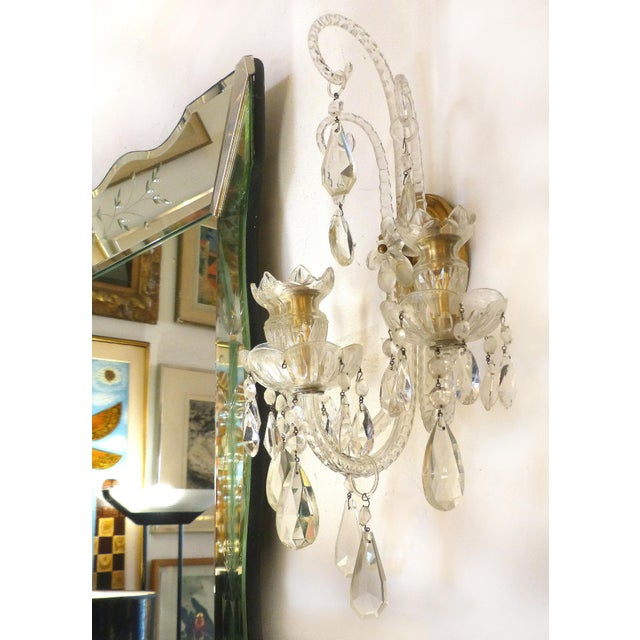 Offered for sale is a fine pair of elegant crystal and bronze electrified three arm wall sconces from the 1940s....