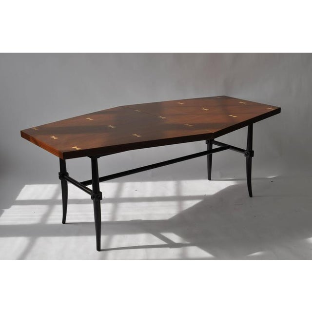 Rare dining table by Tommi Parzinger. Mahogany top with holy butterfly inlays though out. Flared sabre leg. Table measures...