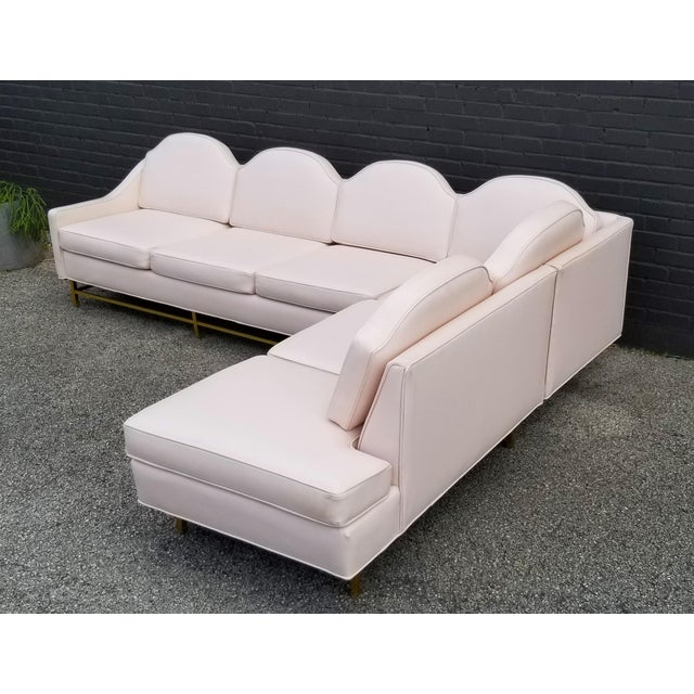Upholstered in a blush-colored leatherette, this sectional sofa is the ultimate in 1960s Palm Springs Hollywood Regency....