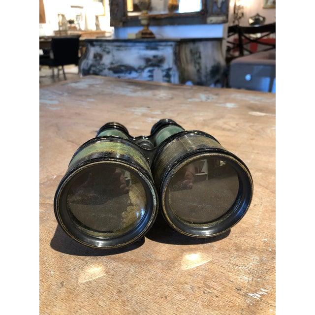 Antique binoculars with a green and black painted metal exterior and focus adjusting mechanism. This pair of binoculars...