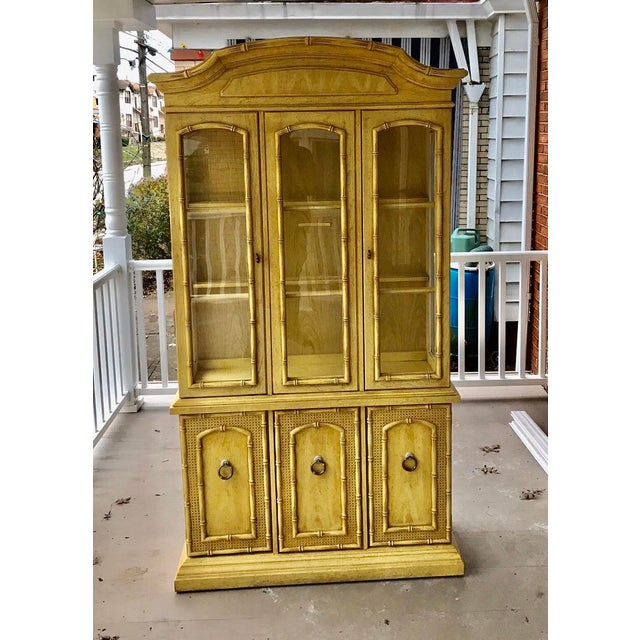 Up for sale is a hollywood regency faux bamboo Thomasville china cabinet. This cabinet breaks down into two pieces.
