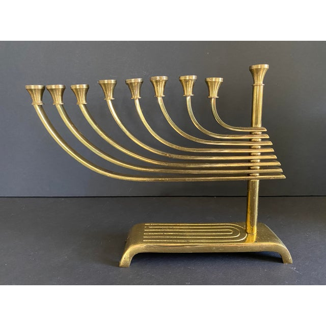 A wonderful mid-century brass menorah by Wainberg of Jersusalem. This Menorah features 8 swiveling arms to create many...