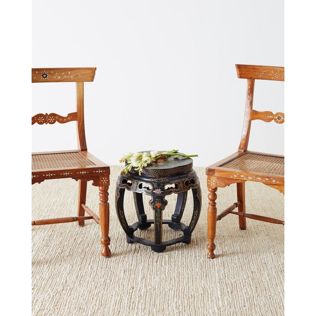Lacquered pair of Chinese garden seats or drinks tables. Featuring a black lacquered finish with decorative Asian motif...