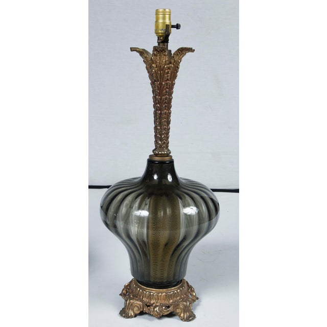 A Fine pair of Italian Venetian glass lamps with gilt base and top. Having smoked sculpted glass integrated with gilt....