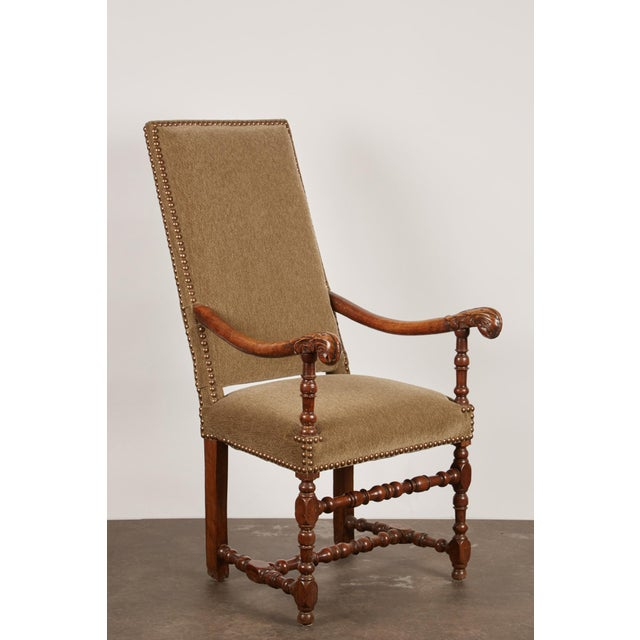 A 17th c. French carved walnut arm chair with handsomely painted turned front legs and stretchers. Each arm features a...