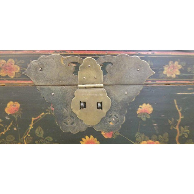 Early 20th century Chinese trunk on stand with butterfly hardware and brass handles. Hand painted floral detail with...