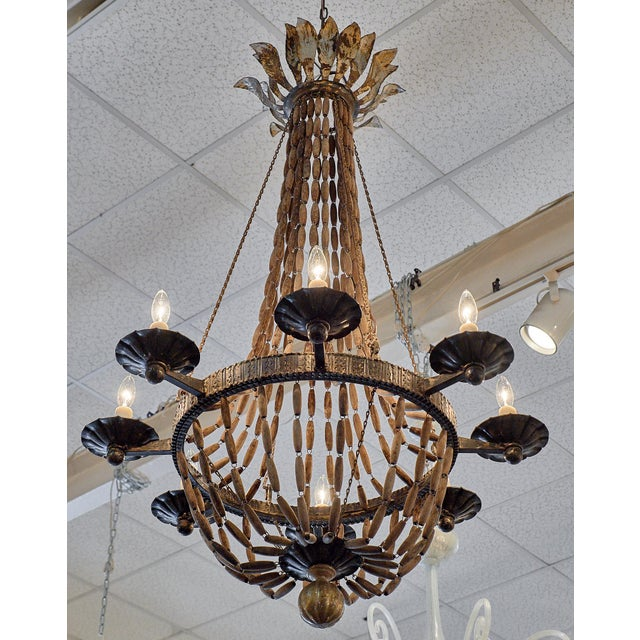 An important Italian chandelier of hand hammered forged iron, wooden beads and chain. This piece has eight branches and...
