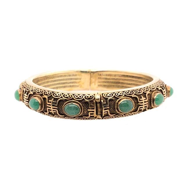 A fine vintage gilt silver Chinese bangle bracelet with bezel set cabochon jade ovals. The bracelet has 12 jade pieces set...