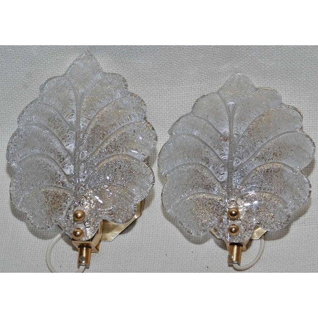 A pair of sconces, glass probably by Orrefors, circa 1960. Brass and handblown frosted glass. Designed for one candelabra...