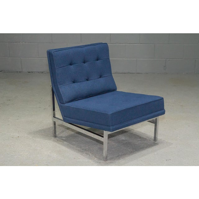 Armless lounge chair by Florence Knoll upholstered in blue fabric with chrome legs and supports.