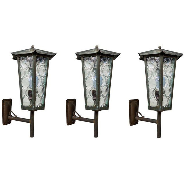1950s Scandinavian outdoor wall lights in patinated copper and glass. Designer unknown. Executed in richly patinated...