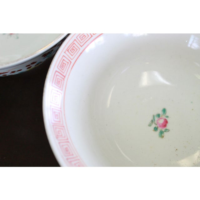 Pair of floral patterned hand painted Chinese rice bowls with orange key design in interior rim.