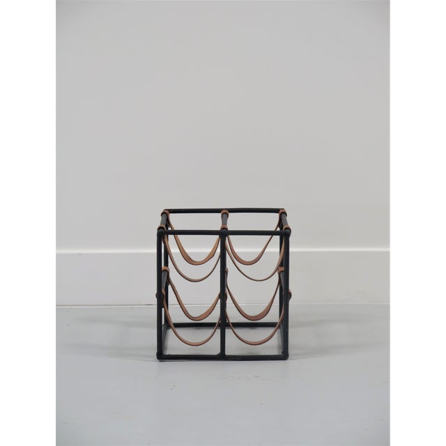 Arthur Umanoff wine rack made of black iron and saddle brown leather straps with brass rivets.