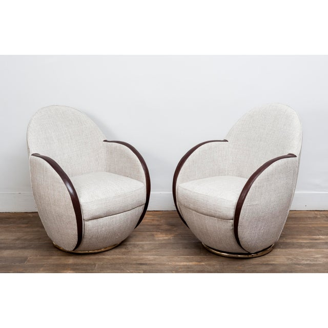 A pair of swivel chairs. Re upholstered with fabric and leather. Base and back handle in brass. Provenance : Cruise ship...