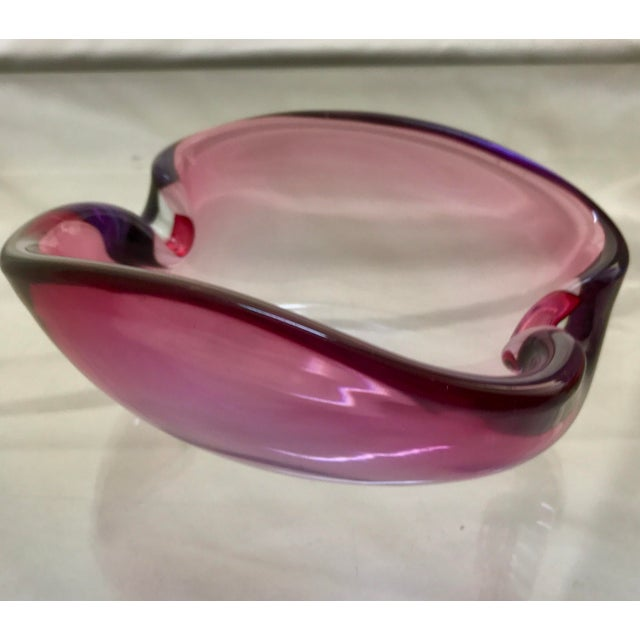 Beautiful small trinket bowl or ashtray hand blown and formed. Pink/ Amethyst in color on edge with clear bottom.