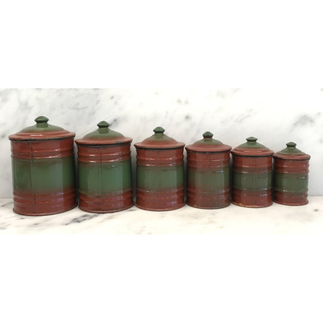 This French enamel canister set consists of six red and green lidded canisters. The canisters have white lettering for...