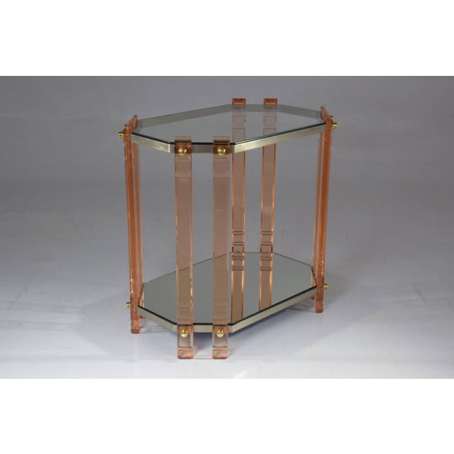 A 20 century French vintage storage piece, accent table, étagère or bar cart composed of a light pink plexiglass structure...