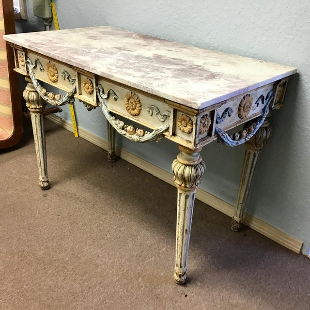 A finely carved, Italian Louis XVI style carved and painted console table with a marble top. The marble top over a deep...