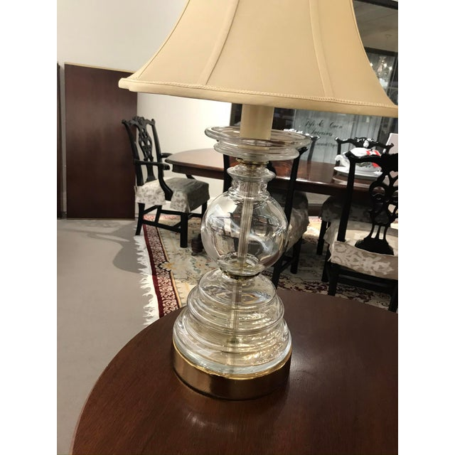 Pair of beautiful glass lamps. These lamps consist of one large hollow glass base that is attached to a metal base. There...