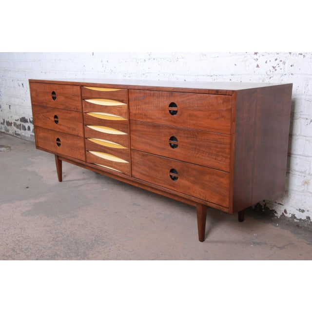 An exceptional mid-century modern Arne Vodder style walnut triple dresser or credenza by West Michigan Furniture Co. The...