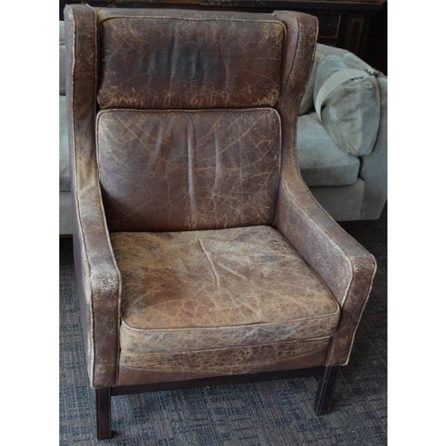 Leather club wingback chair from Edwardian England, early 20th century. The worn leather of this chair has such a hand as...