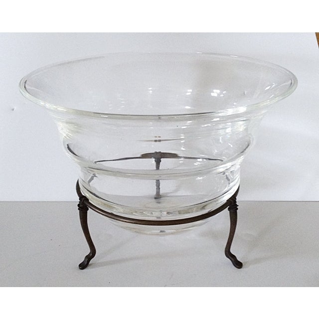 Circular flared glass bowl elevated on tripod metal stand with pad feet.