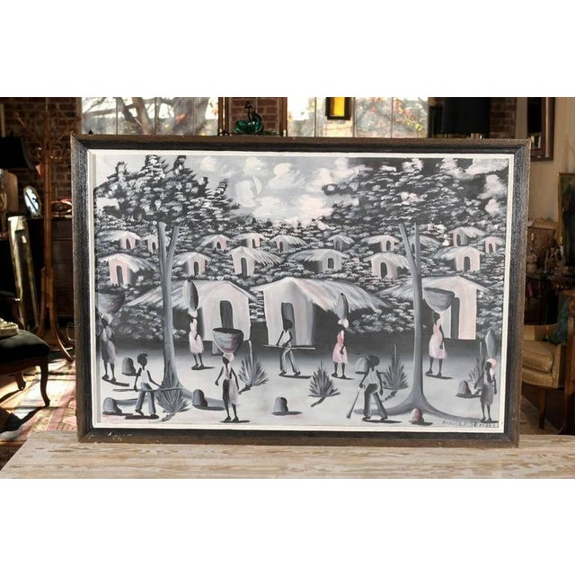 20th century Haitian oil on canvas of a village painted in hues of black, white, grey, and pale pink. Signed by the...