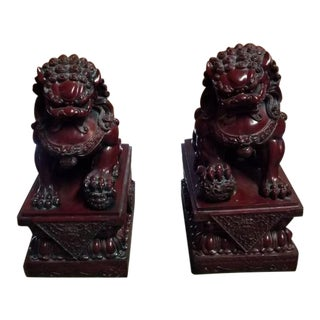 Chinese Faux Cherry Amber Resin Foo Dogs on Wood Stands - a Pair For Sale